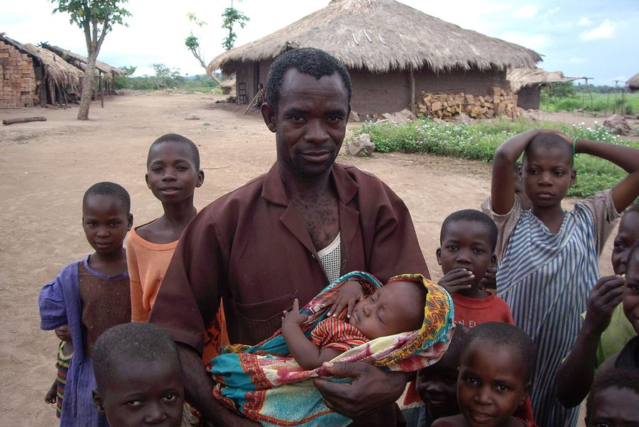 A Congolese man is holding his baby while surrounded by children