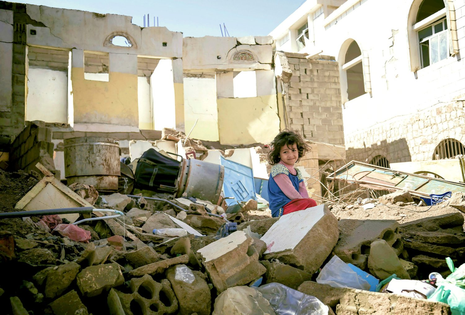 Donate for Yemen: A girl sitting in-between ruins
